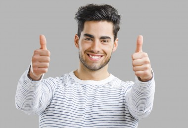 Portrait of handsome young man with thumbs up,  isolated over a gray background