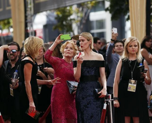 Actress Holland Taylor takes a photo as actress Sarah Paulson (2nd R) prepares for the red carpet at the 67th Primetime Emmy Awards in Los Angeles, California September 20, 2015. REUTERS/Mario Anzuoni