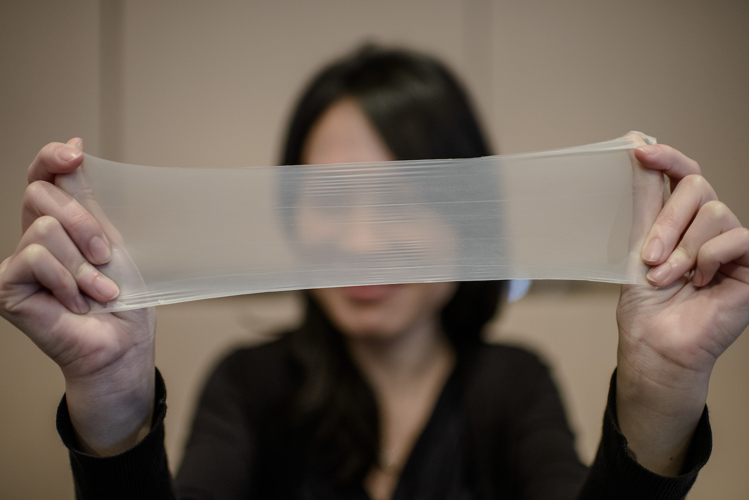 "A woman streches a piece of latex from which the world's thinnest latex condoms are made during a press conference in Hong Kong on February 20, 2014. The condoms manufactured by the Chinese company Guangzhou Daming United Rubber Products Limited are 0.036mm thin on average and listed on the Guinness Records book as the ""thinnest latex condom"". AFP PHOTO / Philippe Lopez (Photo credit should read PHILIPPE LOPEZ/AFP/Getty Images)"