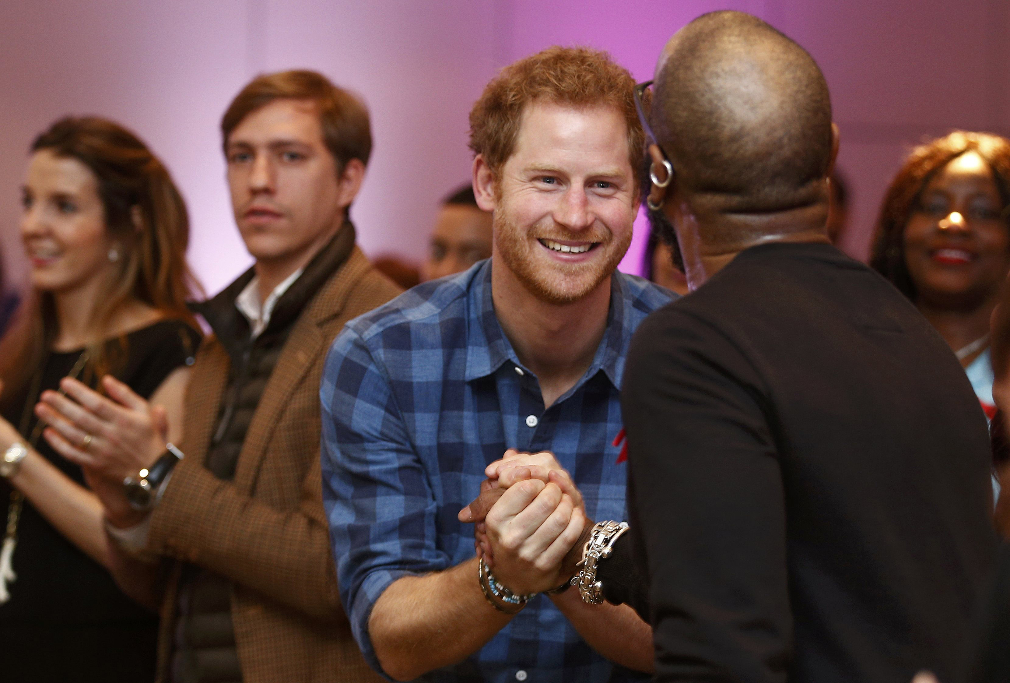 """LONDON, ENGLAND - NOVEMBER 15: Prince Harry congratulates the choir conductor of the """"Joyful Noise"""" choir, a creation of NAZ, a sexual health charity for minority communities, at The Hurlingham club on November 15, 2016 in London, England.  (Photo by Peter Nicholls - WPA Pool/Getty Images)"""
