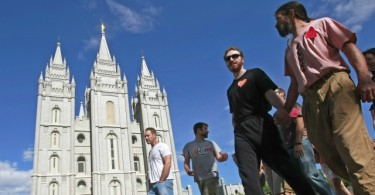 SALT LAKE CITY - JULY 12:  Lionel Trepanier (R) and Lucas Paul (2nd-R) walk past the Mormon Temple on the Main Street Plaza holding hands with other protesters July 12, 2009 in Salt Lake City, Utah. The protesters defied church security warnings and walked onto the plaza anyway to protest the detention and handcuffing of two gay men for holding hands and one kissing the other on the cheek there on July 9. The men were also sited by the Salt Lake City police.  (Photo by George Frey/Getty Images)