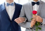 close up of happy male gay couple holding hands