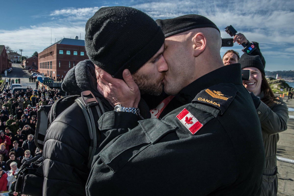 MARPAC photo of Francis Legare kissing partner Corey upon returning home after deployment to Canadian Forces Base Esquimalt