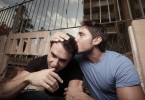 Man comforting his upset boyfriend by kissing him on the head