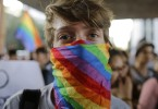 A man cover his face with a scarf with the colors of the gay movement during a protest against the homophobic comments of presidential candidate Levy Fidelix, in Sao Paulo, Brazil, Tuesday, Sept. 30, 2014. Fidelix a minor character in Brazil's election race faced a firestorm of criticism on Monday after saying during a presidential debate that the country needs to stand up against gay people who should receive psychological help far away from the general population. The comments drew no reaction from the leading candidates during the nationally televised debate late Sunday. But online and on social media tens of thousands of people denounced Fidelix as homophobic and hateful. (AP Photo/Nelson Antoine)