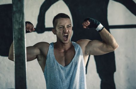 Photo of a young male athlete showing of his muscles after an intense workout.