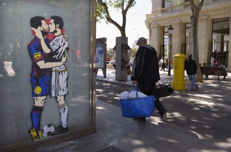 """People pass next to the street art """"Love is blind"""" of Street artist Salva """"Tvboy"""" on April 21, 2017 in Barcelona, which shows Barcelona's Argentinian forward Lionel Messi and Real Madrid's Portuguese forward Cristiano Ronaldo kissing each other two days before 'El Clásico' match between Real Madrid and FC Barcelona. / AFP PHOTO / LLUIS GENE"""